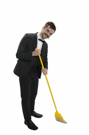 Young man dressed in suit and bowtie sweeping the floor isolated on white