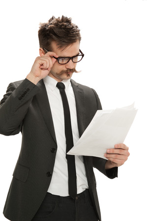 Young man adjusts his glasses while examining business papers, isolated on white background