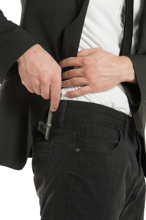 Closeup of a young businessman places a skeleton key in his back pocket, isolated on white background