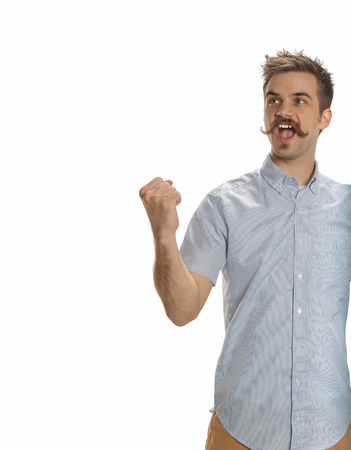 Attractive young man with a handlebar mustache playfully raises his fist in a challenge, isolated on white Banco de Imagens