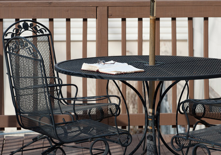 A pair of reading glasses rests on top of an open Bible on a wrought-iron patio table on a wooden deck as the evening shadows settle in  Stock Photo
