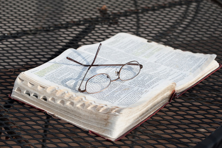 A closeup of a pair of reading glasses resting on top of a worn, open Bible on a wrought-iron patio table