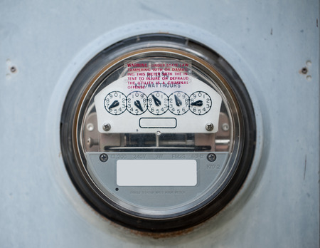 Closeup of a scratched up electric meter in use photo