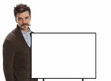 Attractive young man with a handlebar mustache and a brown sweater stands in front of a blank white sign with black border, isolated on white