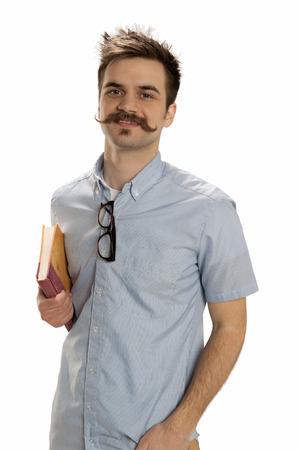beau jeune homme: Beau jeune homme avec une moustache de guidon et lunettes de hippie est titulaire d'un vieux livre Banque d'images