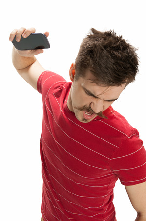 Angry young man throwing his smart phone down, isolated on white Stock Photo