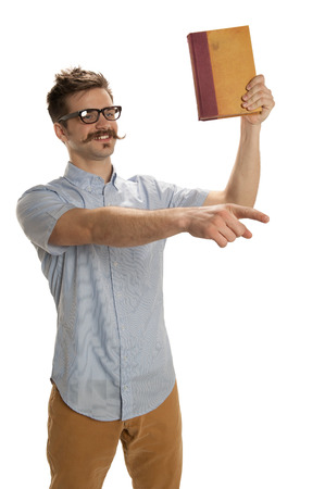 Attractive young man holds an old book up high while preaching and pointing, isolated on white