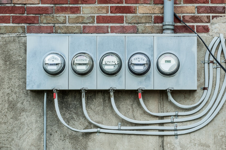 A series of electric meters line the wall of an apartment building