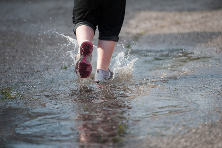 Closeup of water splashing up from a little girls shoes as she runs through a puddle in the street, selective focus on the stream of water behind her shoe.