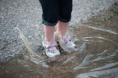 Close up of a little girls filthy legs as she jumps in a puddle, making a huge splash and wave