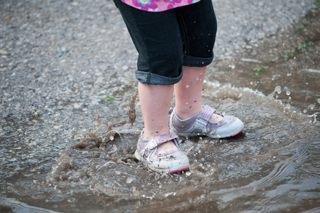 Closeup of a toddlers dirty legs and shoes as she splashes in a rain puddle