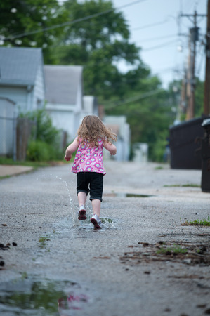 Little girl runs away from the camera, splashing through puddles in an alley