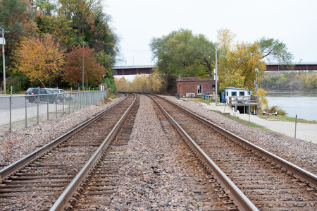 Train tracks leading out of a small rural town disappear around the bend past trees covered in fall leaves