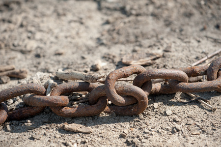 A thick, abandoned chain used for mooring barges or large ships lies on the shores of the mighty Mississippi River.