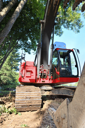 The claw of a frontloader devestates the vegetation growing in a residential neighborhood