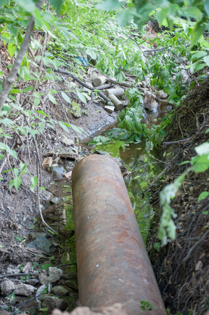 sewer pipe: Rusty sewer pipe feeds into a creek