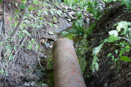 Rusty sewer pipe feeds into a creek