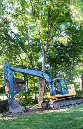 A frontloader prepares to clear trees from a creek in a residential neighborhood