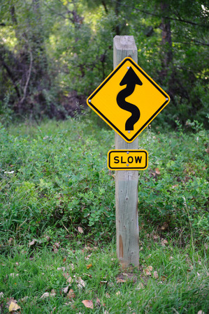 A snake sign in the grass warns of curves in the road ahead Stock Photo