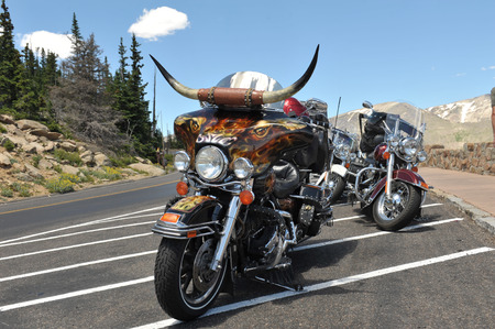 Three fancy motorcycles resting atop a mountain viewing area Stock Photo