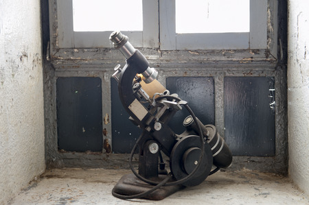 An outdated microscope sits on the window sill in a medical cell of an abandoned prison penitentiary. Stock Photo