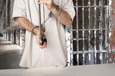Closeup of a man in prison using a hacksaw to escape from his handcuffs