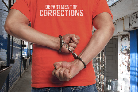 Closeup of a man in prison using a hacksaw to escape from his handcuffs photo
