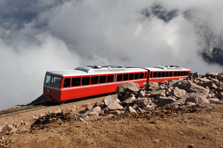 Tram carries tourists up the steep incline of Pikes Peak, through the clouds
