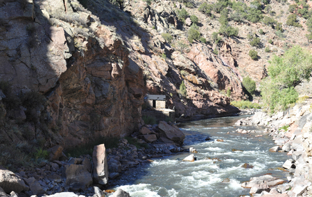 White water river flowing past an abandoned mining cabin in Colorados Royal Gorge Stock Photo