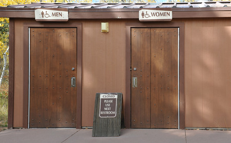 latrine: Outdoor bathrooms marked men and women with a sign saying closed, please use next restroom