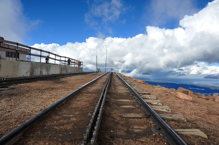 Train tracks atop Pikes Peak end abruptly at the edge of a cliff high above the valley below Stock Photo