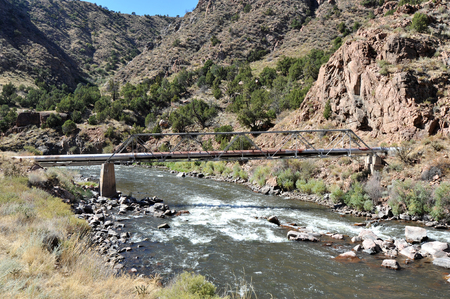 White water river flowing under a utility pipe and through Colorados Royal Gorge Stock Photo