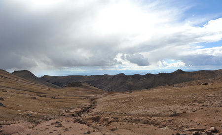 A barren landscape marks the top of a mountain in the Rockies as a storm moves in.