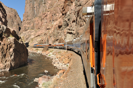 White water river flowing through Colorados Royal Gorge as a train rounds the bend
