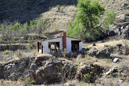 An abandoned and collapsing house at the bottom of a mountain hearkens back to an earlier time Stock Photo