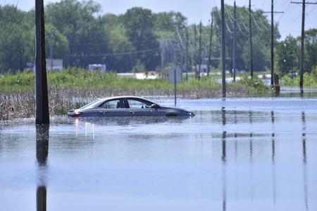 Un coche se sienta varado después de conseguir atascado en una carretera inundada Foto de archivo - 78735918