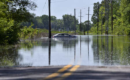 Ein Auto sitzt gestrandet, nachdem es auf einer überfluteten Straße festgefahren ist Standard-Bild - 78566470