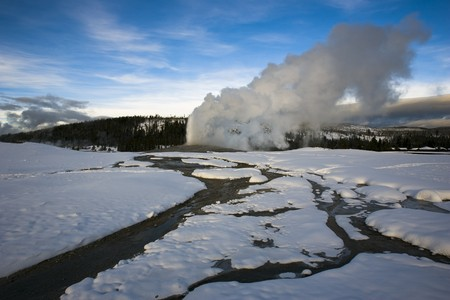 Old Faithful Geyser erupting in winter at Yellowstone National Park Stock Photo