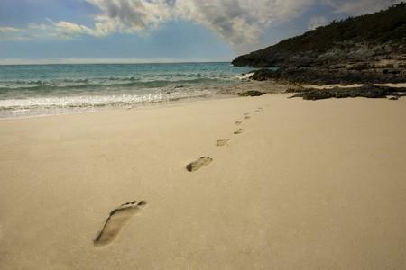 Footprints on a beach heading to the ocean