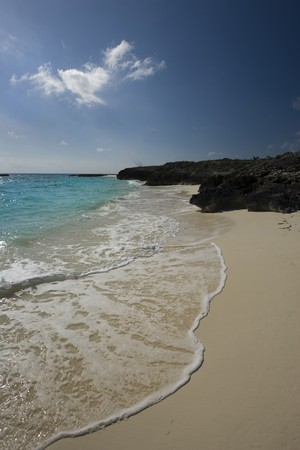 A stretch of sandy beach with a fan of ocean wave in the Caribbean Stock Photo