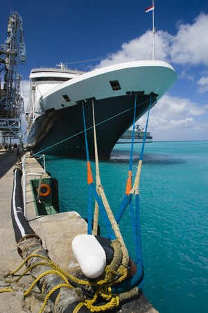 A cruise ship tied to a dock in Caribbean water