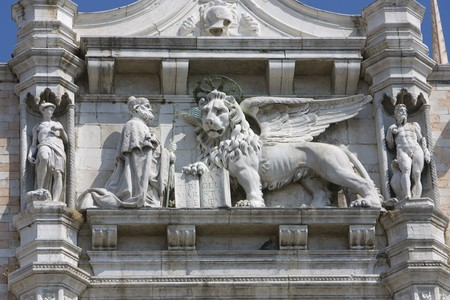 A Lion and holy man sculpture on Venice, Italy building