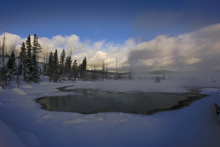 A Steaming hot pool at Yellowstone National Park in the early morning of Winter snow.