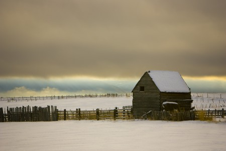 An old barn and fencing with storm clouds and winter snow