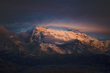 Mount Timpanogos, Utah, lit with brilliant light from a beautiful cloud covered sunset