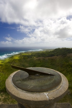 A sundial overlooks the ocean waves with storm clouds in the sky
