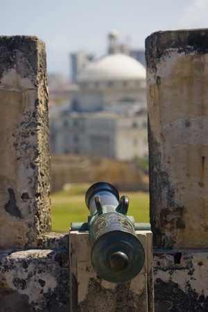 An old canon, between turrets is  pointed at a soft focus city