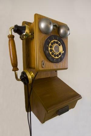 A Vintage rotory telephone on a plain wall
