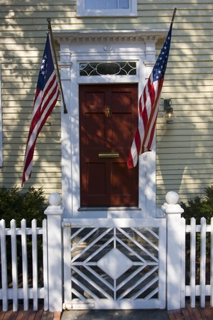 Two american flags flying on a door with a pickett fence forground