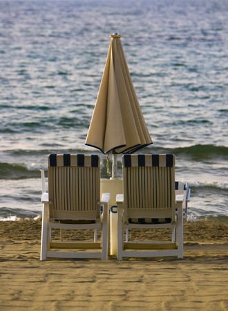 Two beach chairs and an umbrella on groomed sand at the sea shore